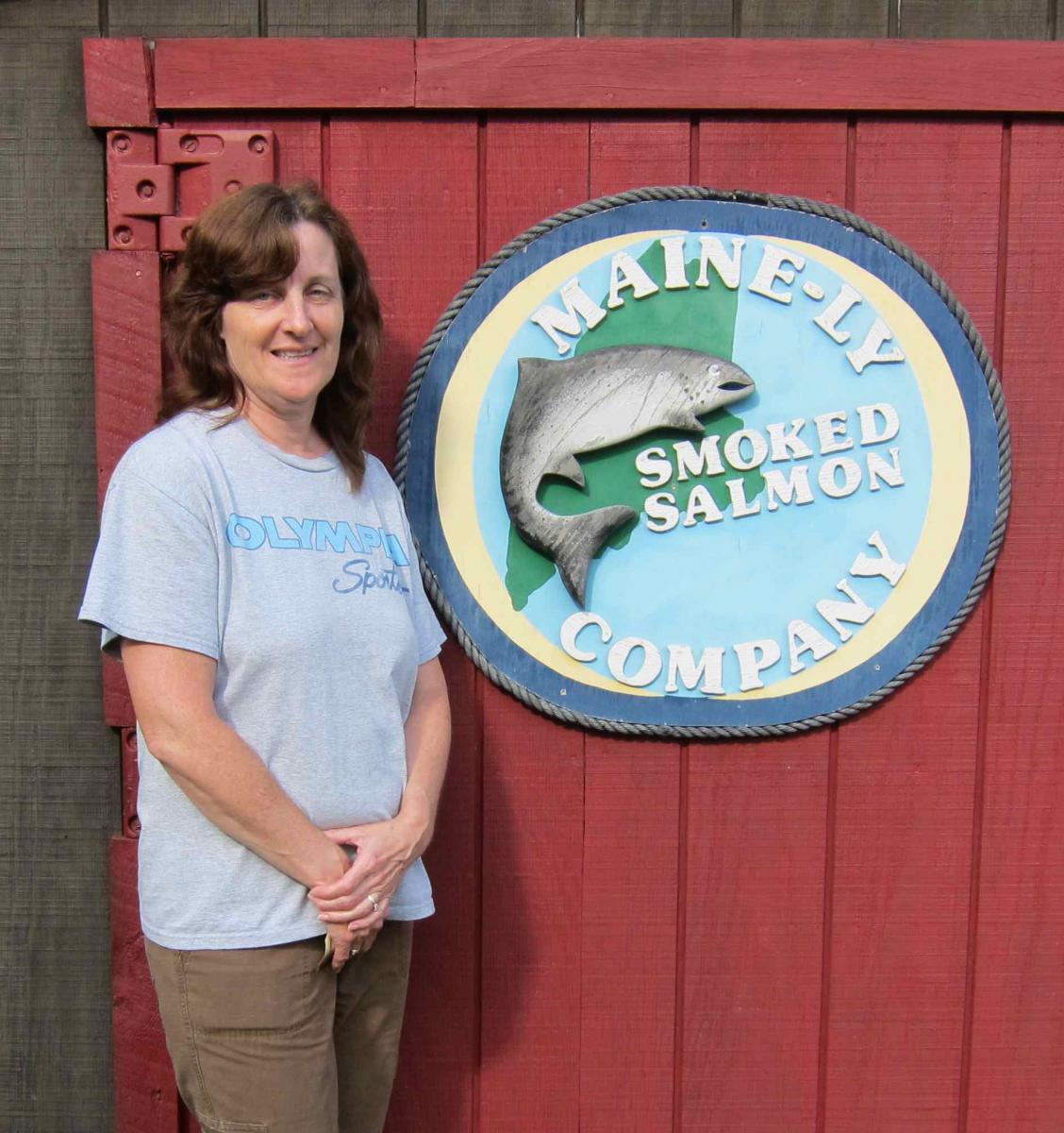 Karen Constant standing next to Mainely Smoked salmon sign