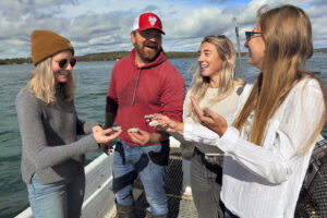 Four people smiling and holding out oysters to eat on a boat