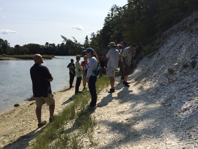 Workshop participants stand at the base of the shell midden, with the Damariscotta River and trees in the background.