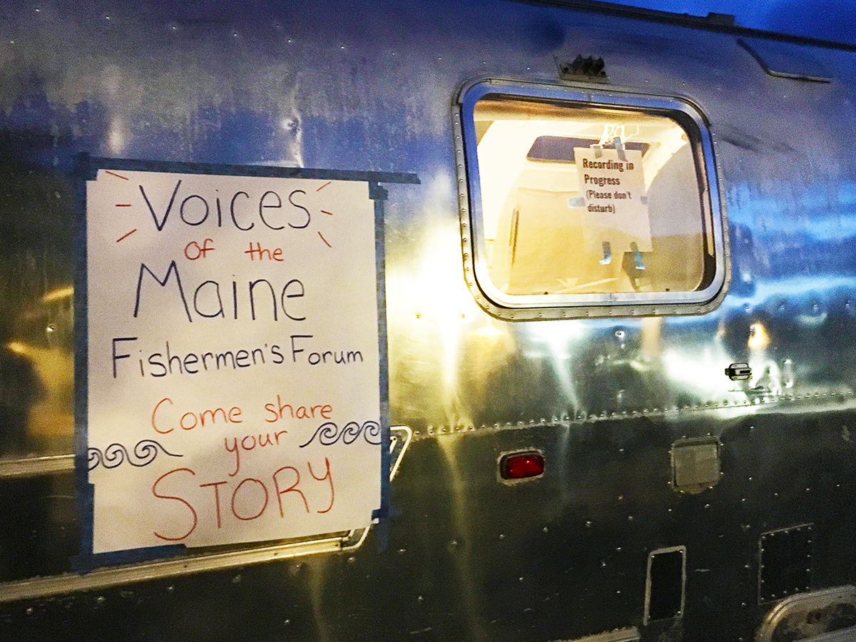 A handwritten sign on the window of an Airstream trailer reading 'Voices of the Maine Fishermen's Forum - Come share your story'