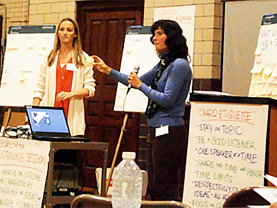 two women, one with a microphone, standing among flipcharts