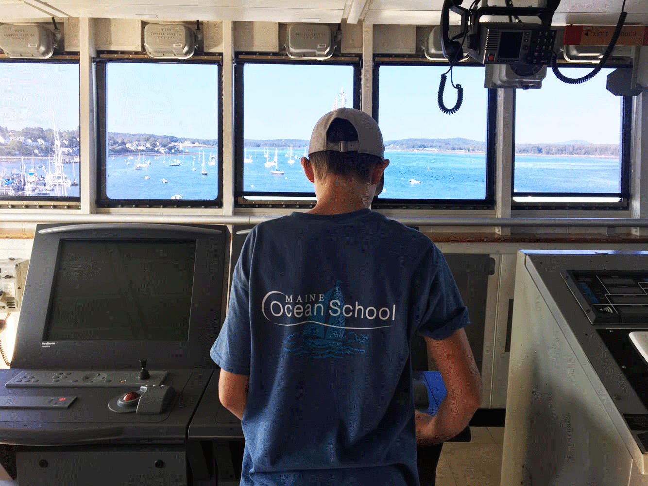 a teenager at the helm of a boat wearing a Maine Ocean School t-shirt