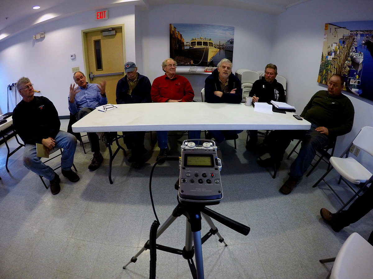 photo of fishermen sitting around audio recording equipment