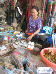 A woman behind a table covered in packaged items for sale