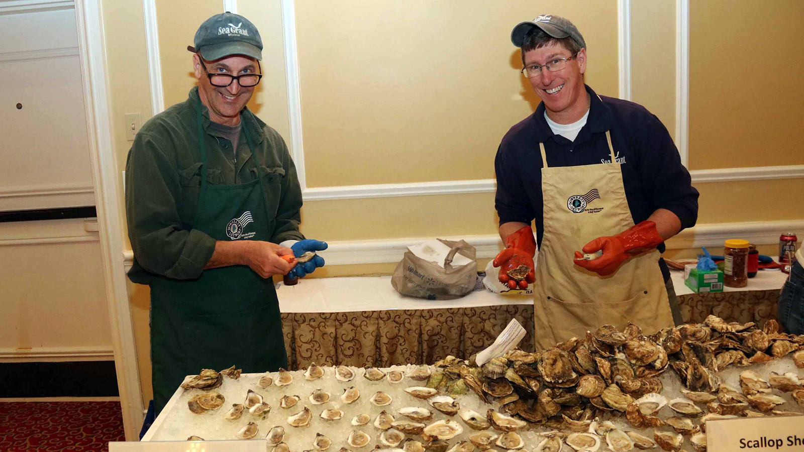 Two smiling men shucking shellfish behind a table of scallops and oysters on the half-shell