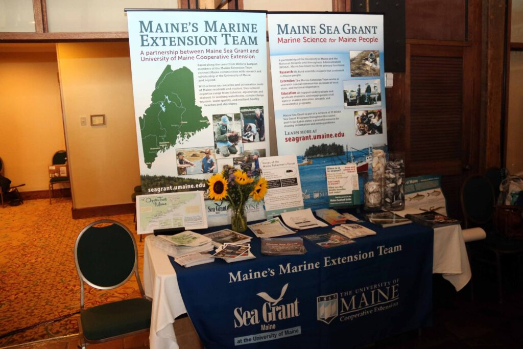 A display table holds 2 Maine Sea Grant banners, a bouquet of flowers, and information pamphlets and handouts.