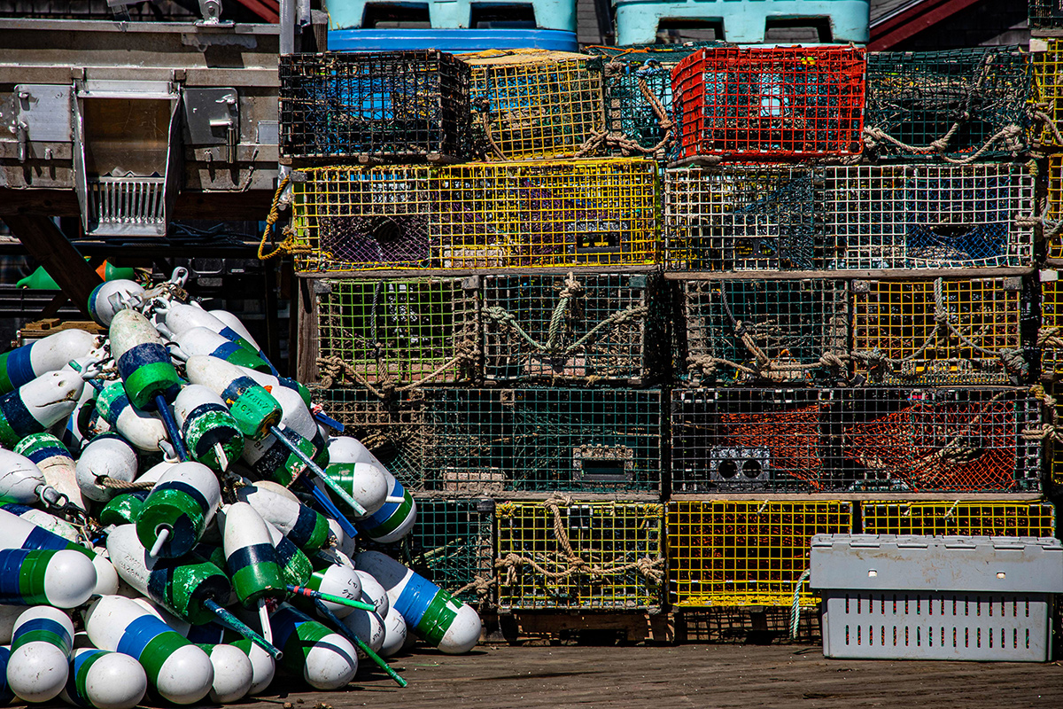a pile of buoys next to a pile of lobster pots