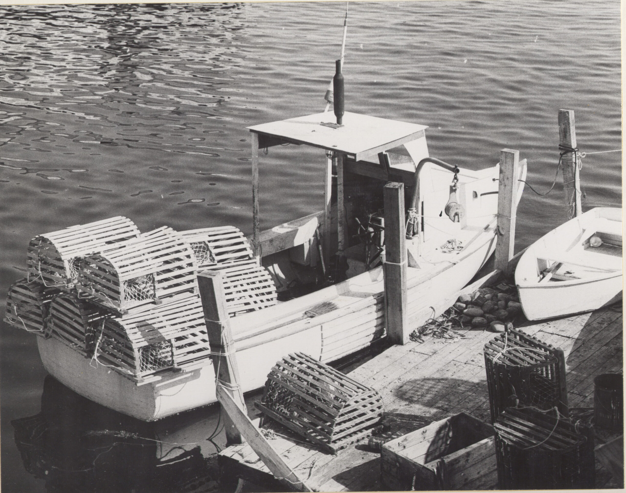 black and white historic photo of a moored lobster boat