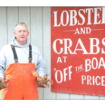 """lobsterman holding a lobster in each hand in front of a sign reading 'Lobster and Crabs at """"off the boat"""" prices'"""