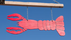 a hand painted lobster sign against the blue sky