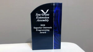"blue award on table reading ""sea grant extension assembly 2020 superior outreach programming award"""