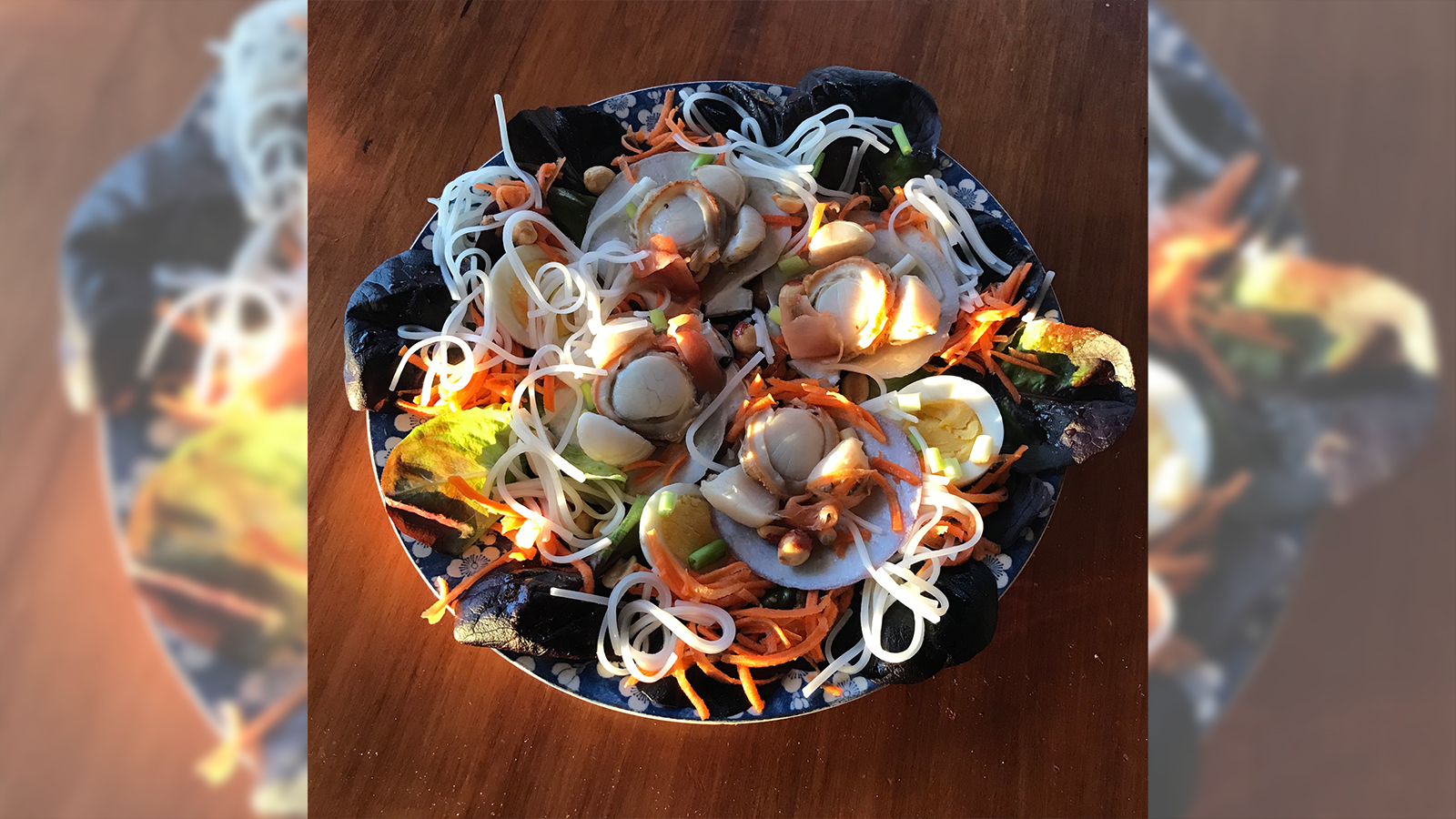 Bowl with scallops, noodles, salad greens, carrots, hard-boiled eggs, and other food items. The bowl is set on a wooden surface.