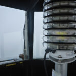 Close up of lighthouse lens, from inside tower. Foggy background