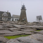 Lighthouse keepers house and Mount Desert Rock Light Tower, view from the northwest. Granite ledge, Foggy background.