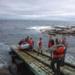 People in life jackets and a zodiak inflatable boat on a boat ramp at the edge of the ocean. Overcast sky.