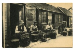 Four men sitting in front of buckets full of shellfish with empty buckets next to each of them.